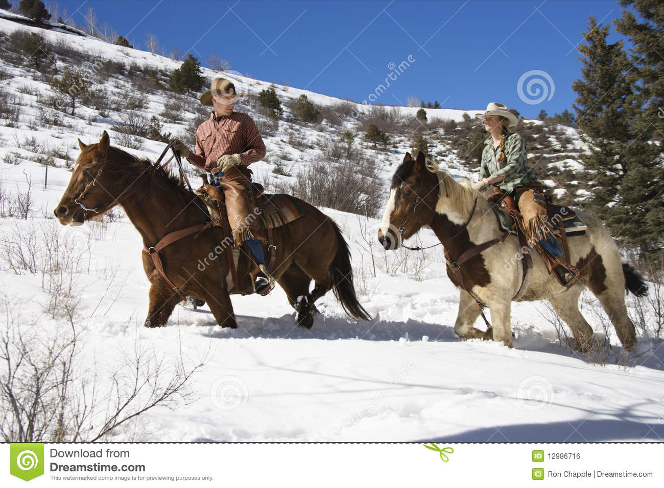 Man And Woman Riding Horses In The Snow Royalty Free Stock