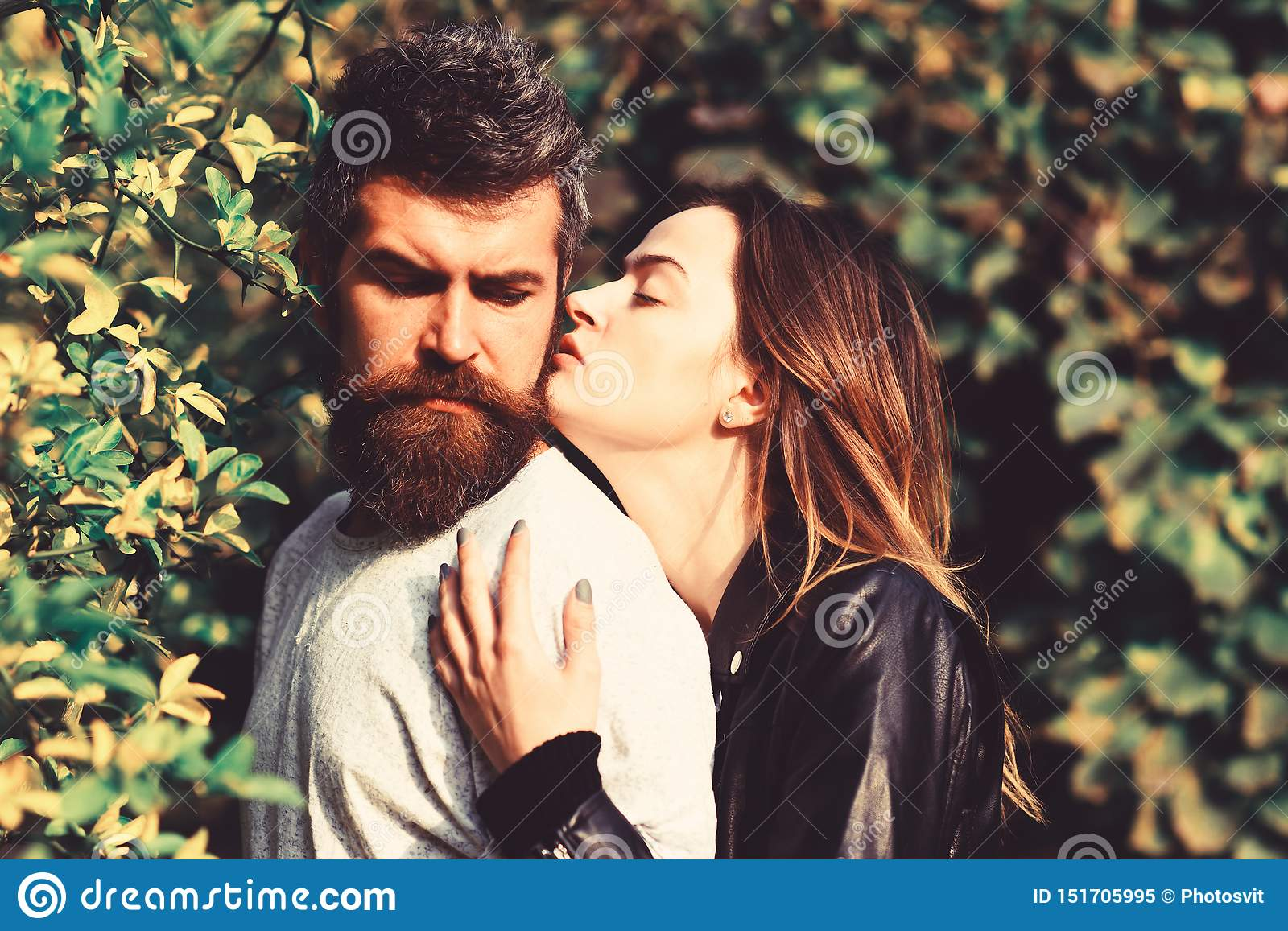 Man and woman with romantic faces on autumn trees background.