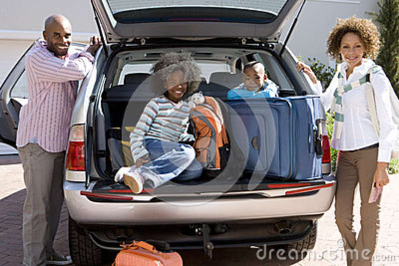 Man and woman by son and daughter (6-10) in back of car with luggage, smiling, portrait