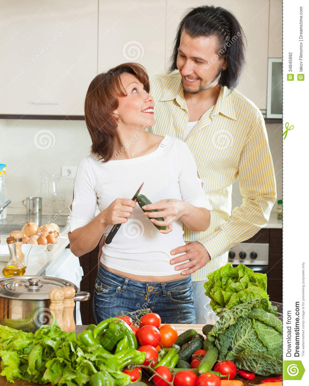 Women Kitchen: A Man And A Woman With Vegetables In The Kitchen Stock