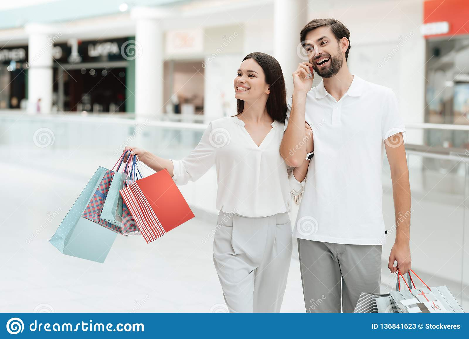 Man and woman are walking to another store in shopping mall. Man is talking on phone.