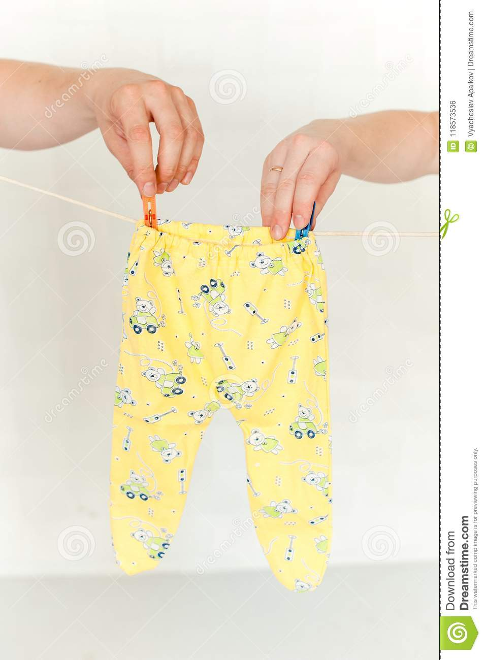 Man and womans hand pinning a romper