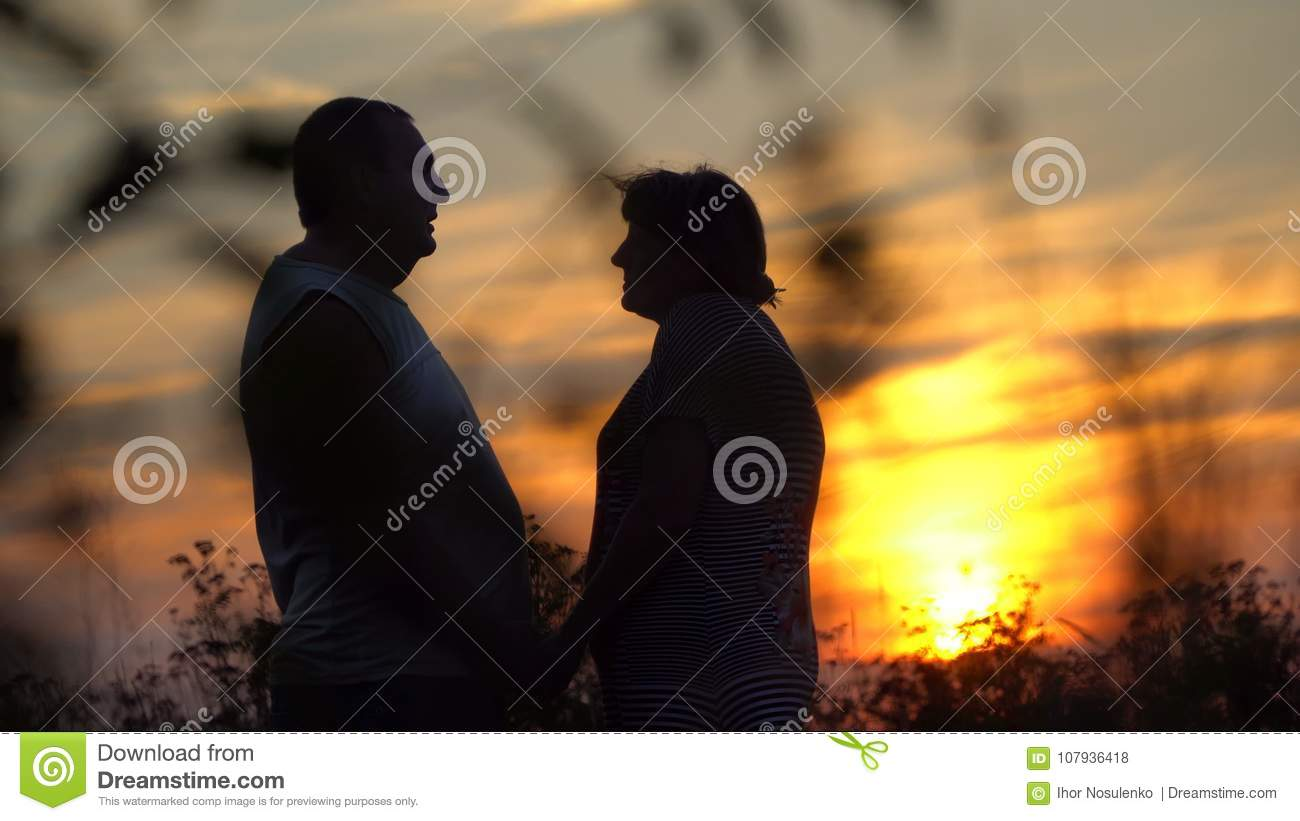 Man and woman facing each other on the sunset background