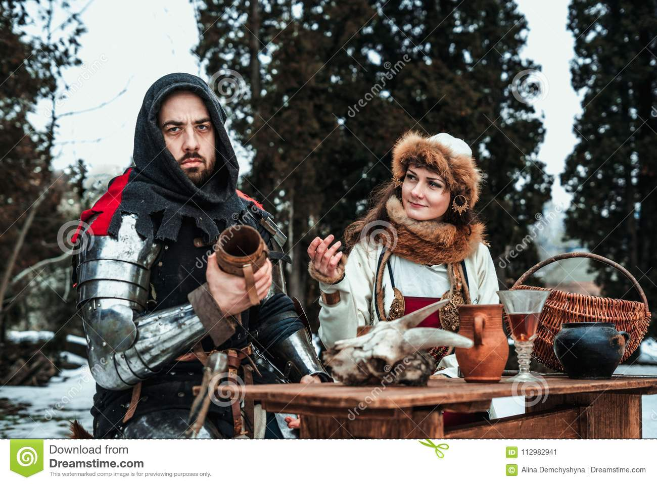 A man and a woman in historical costumes are sitting at a table