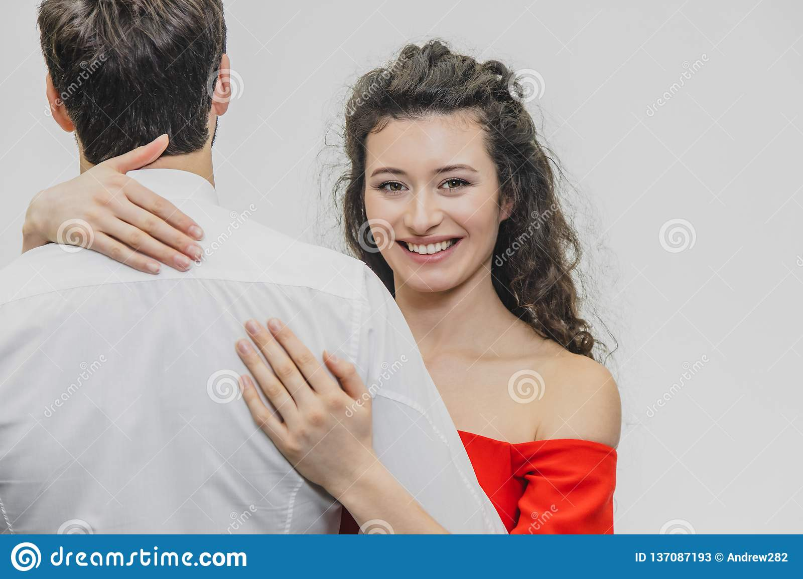 Man and woman with long hair. The wife hugged her husband. Back view. Valentine`s Day. I Woman dressed in red man dress