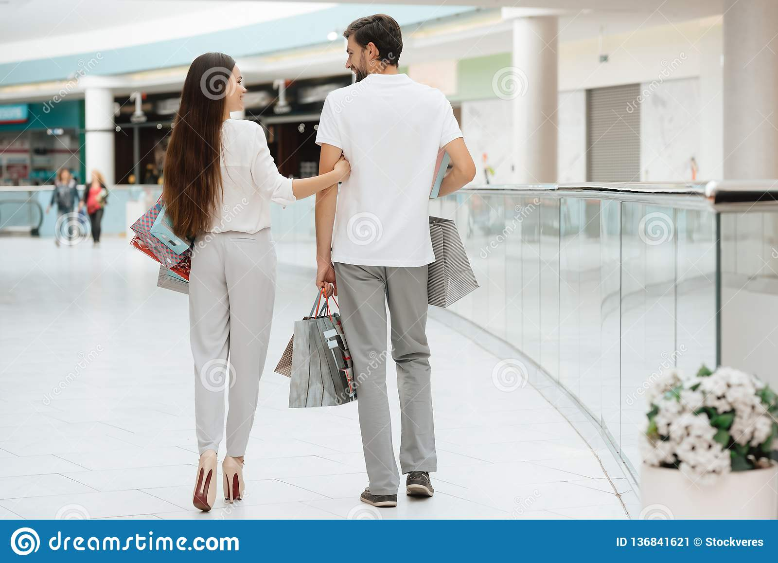 Man and woman are walking to another store in shopping mall. Couple is happy.