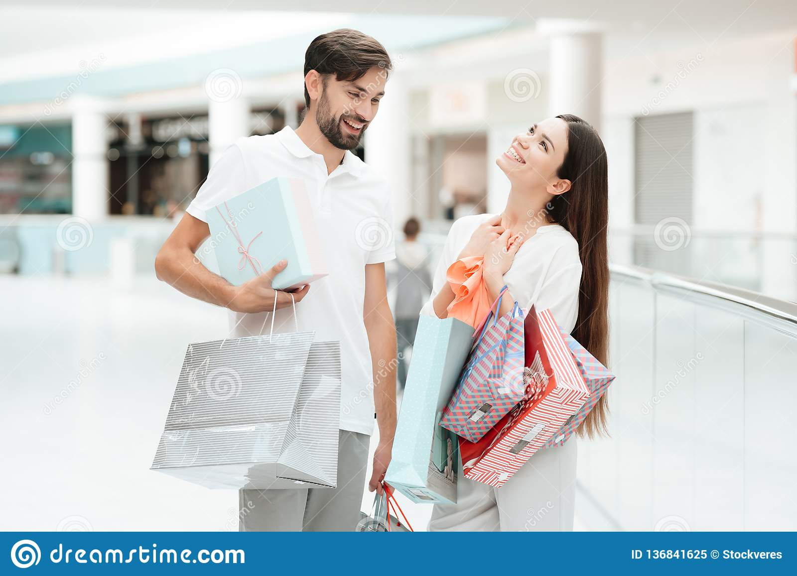 0c69e76ff5 Man and women with shopping bags are walking to another store in shopping  mall. Couple is happy.