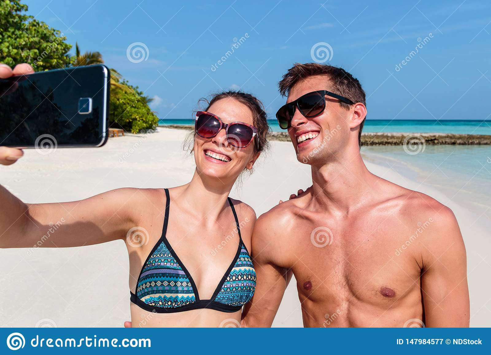 Happy young couple taking a selfie. Tropical island as background