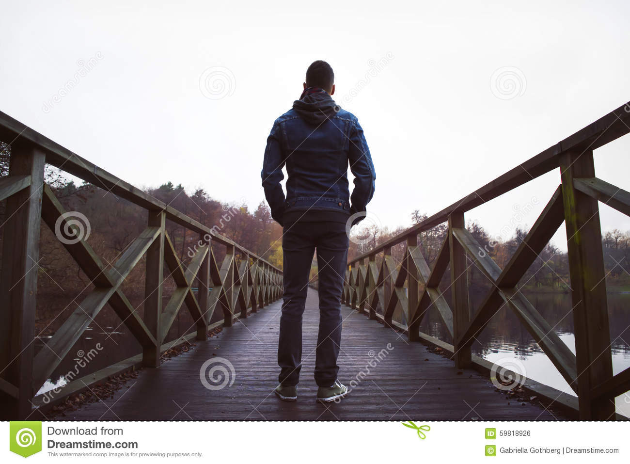 Man On Wooden Bridge Over A Lake On A Damp Autumn Day