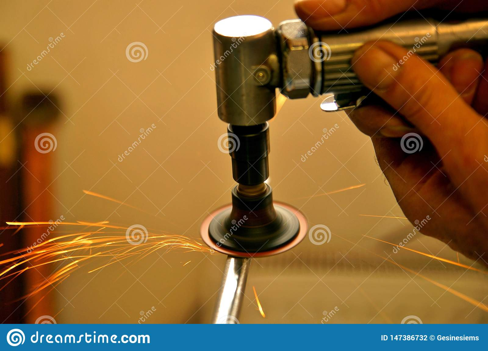 A man working with air pump grinder cleans metal parts blanks.