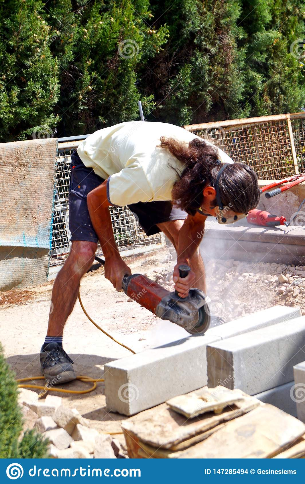 A man working cutting concrete block with electric saw hand working.