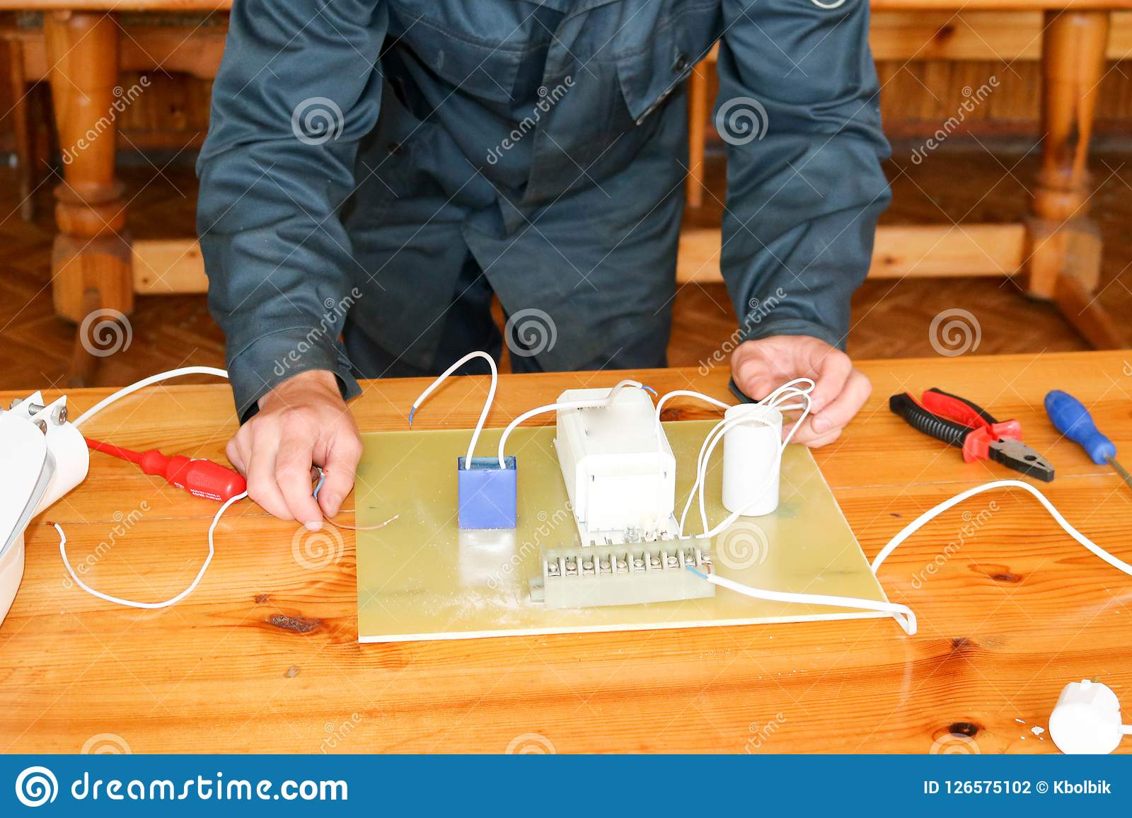 Awesome A Man Working Electrician Works Collects The Electric Circuit Of A Wiring Digital Resources Instshebarightsorg