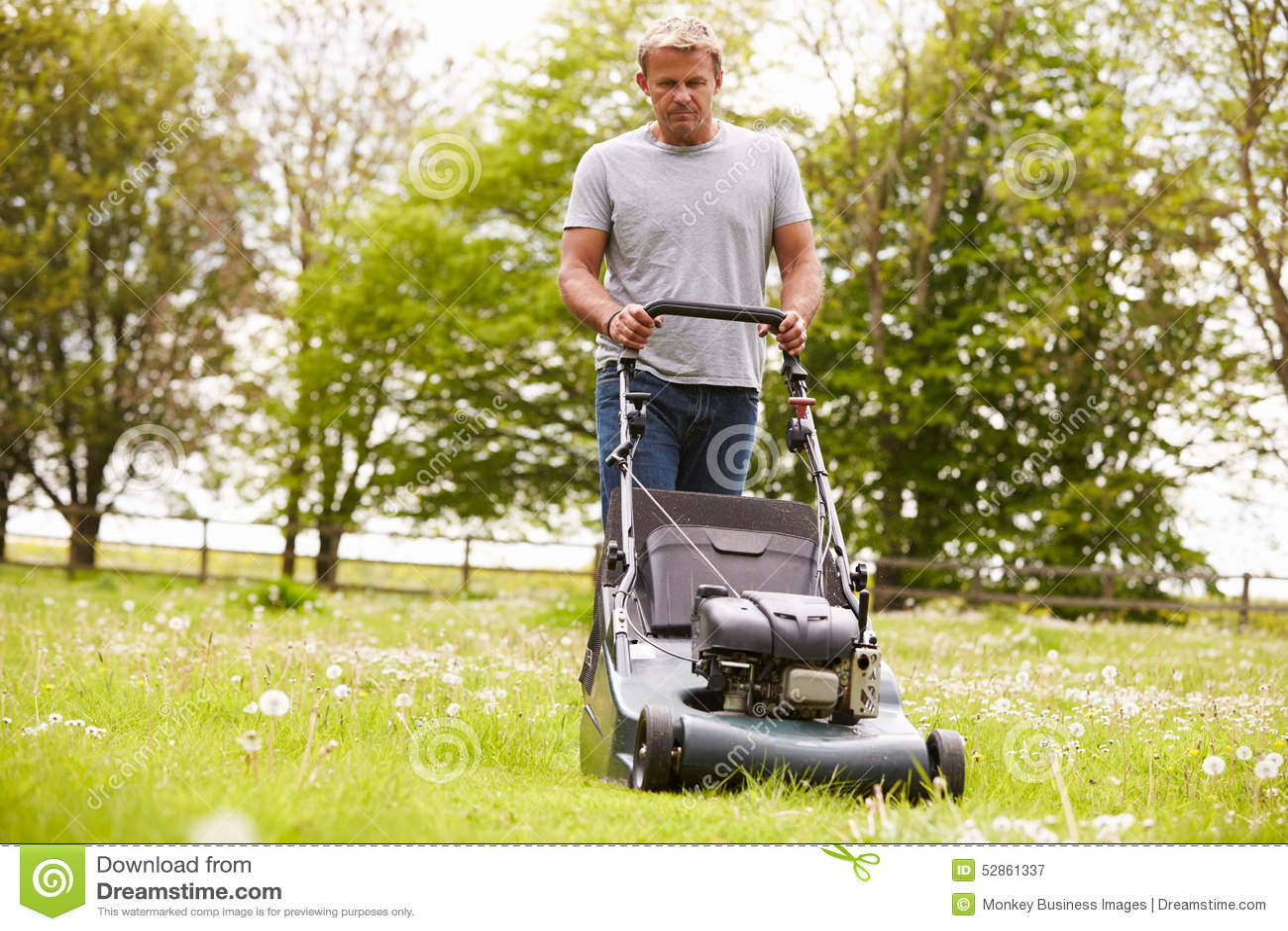 Man working in garden cutting grass with lawn mower stock for Lawn mower cutting grass