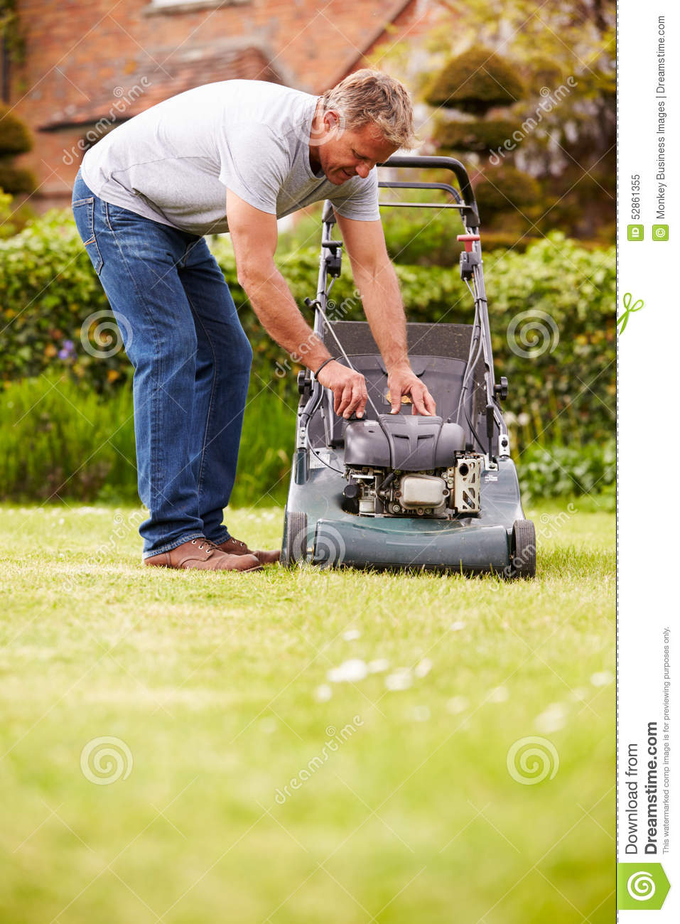 Young man mowing the grass stock image. Image of back