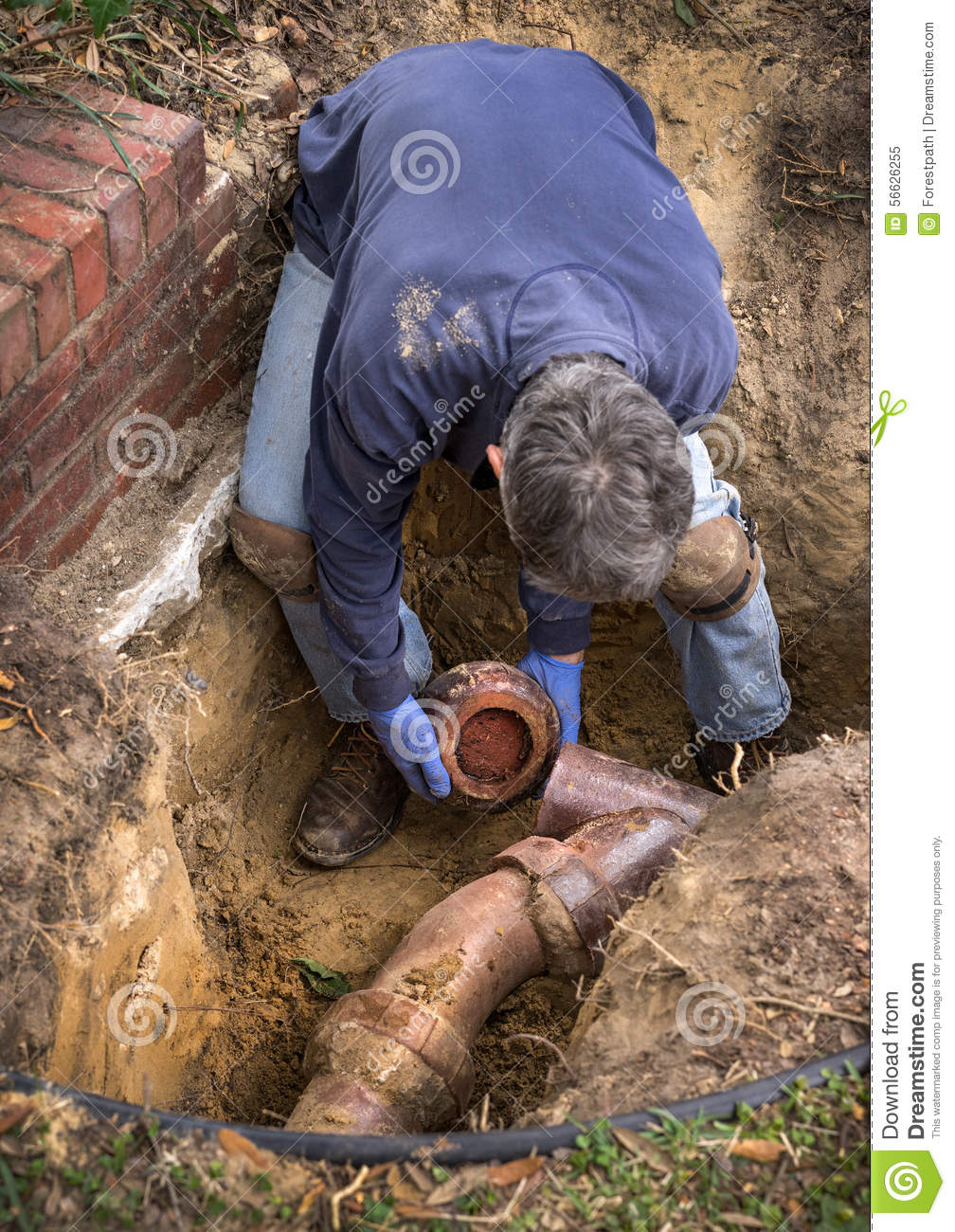 Man Working On Old Clay Ceramic Sewer Line Pipes Stock