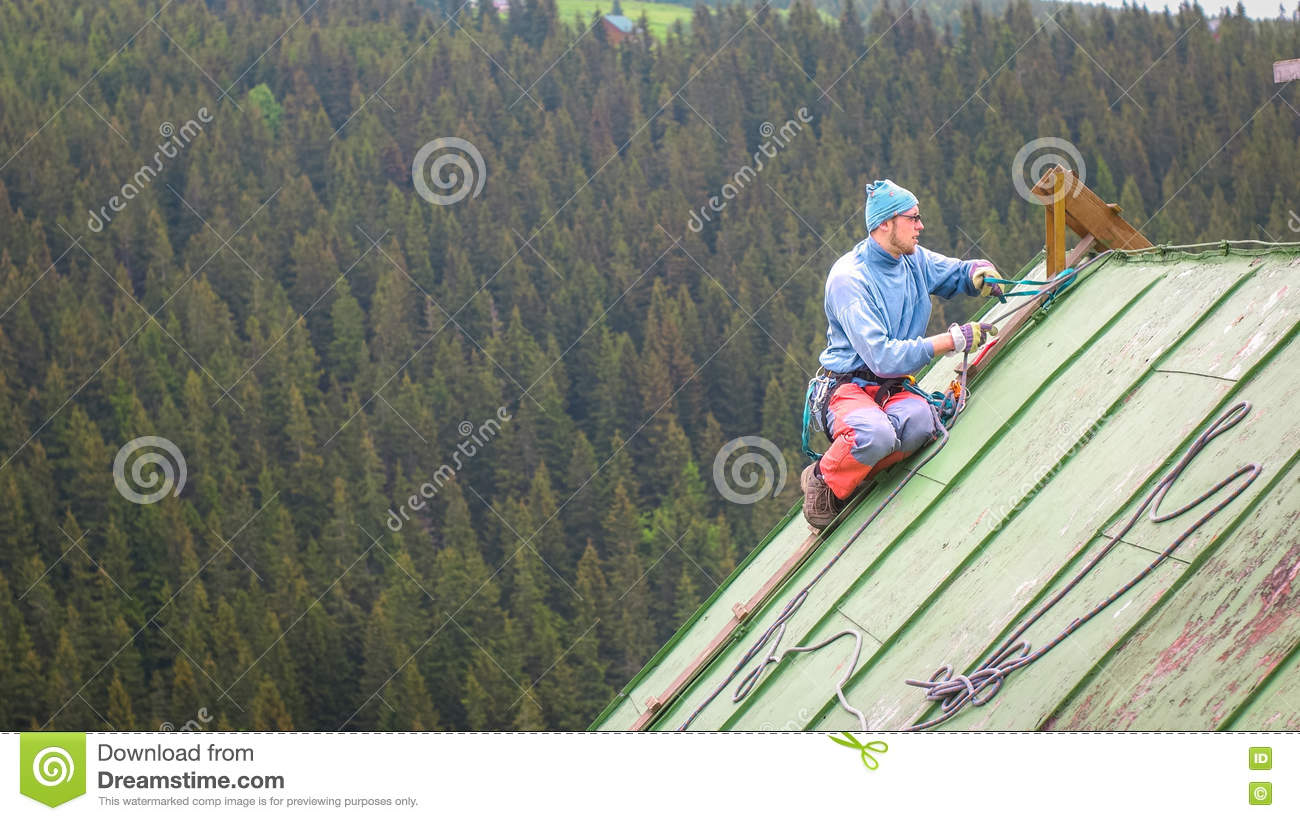 Man Working On The Roof Checking Safety Gear Stock Image