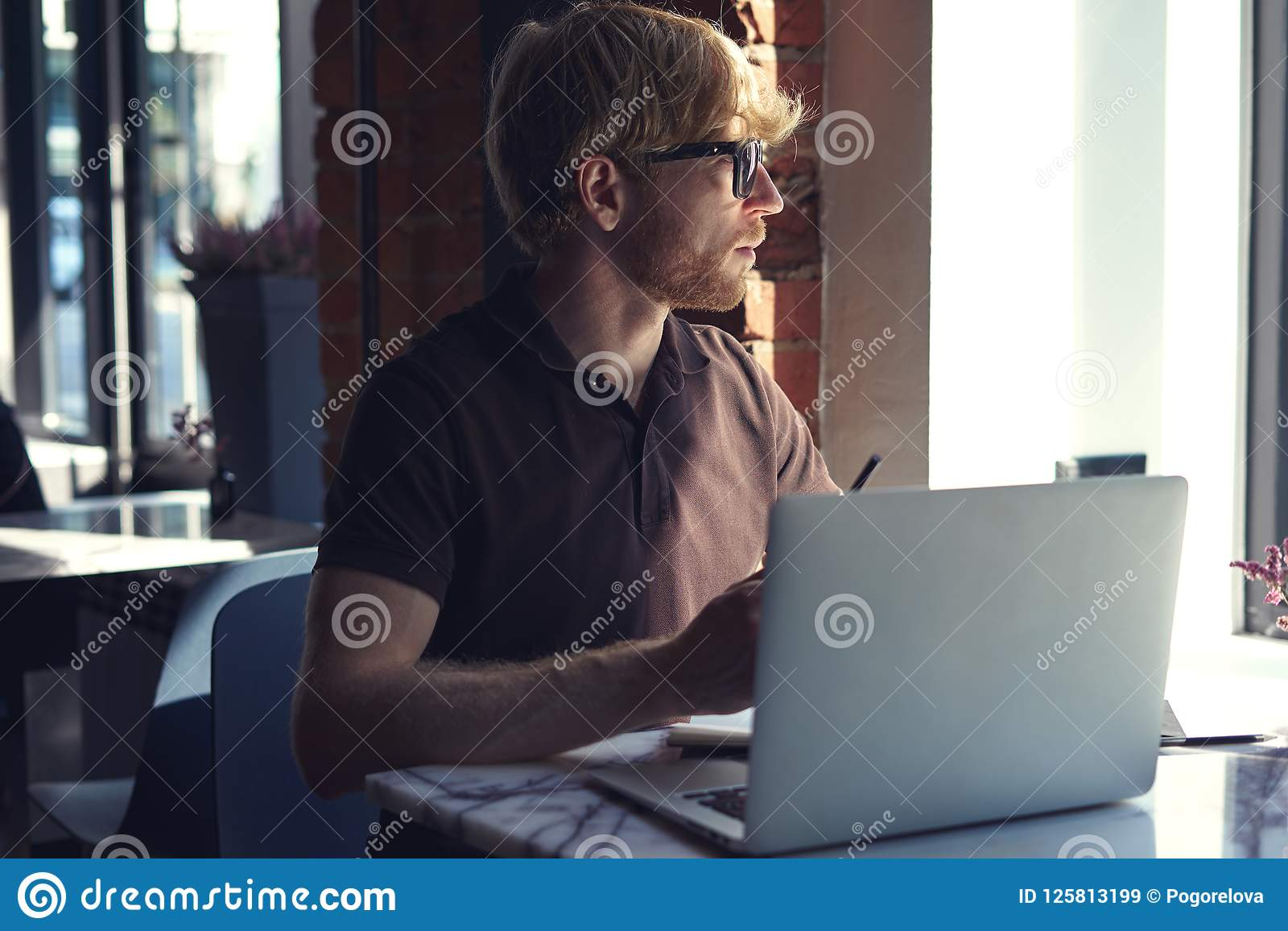 Man working at sunny office on laptop while sitting in cafe having coffee. Concept of young business people