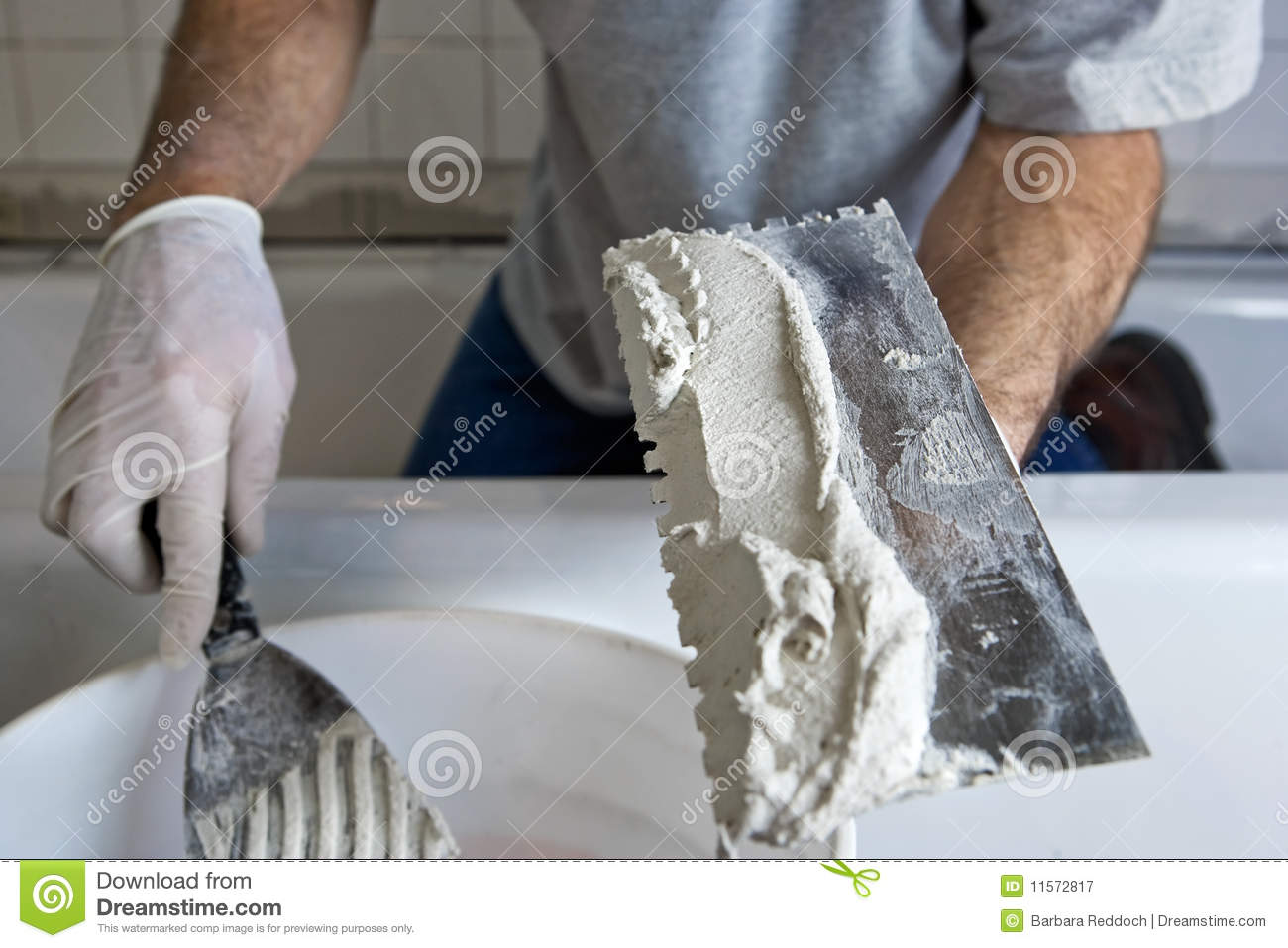 Man Working with Trowel and Mortar Tiling a Wall