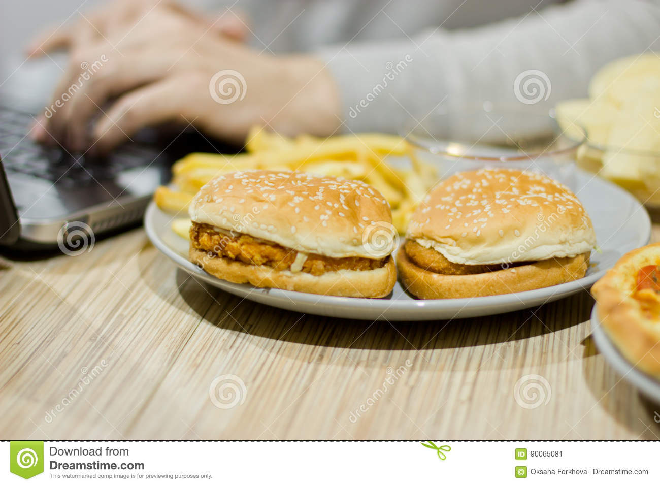 A man works at a computer and eats fast food. unhealthy food: Bu