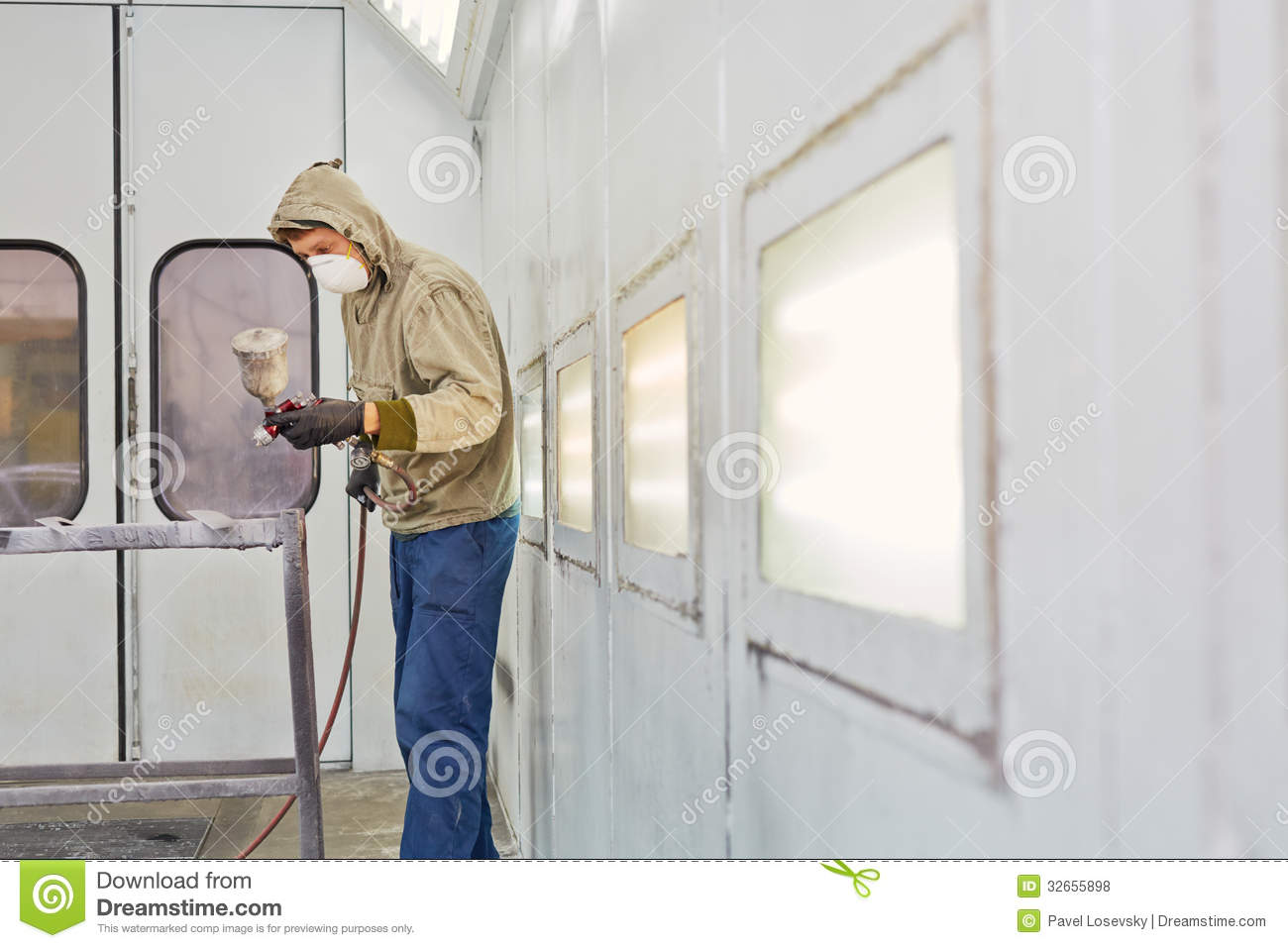 Man works in paint-spraying booth, painting car details