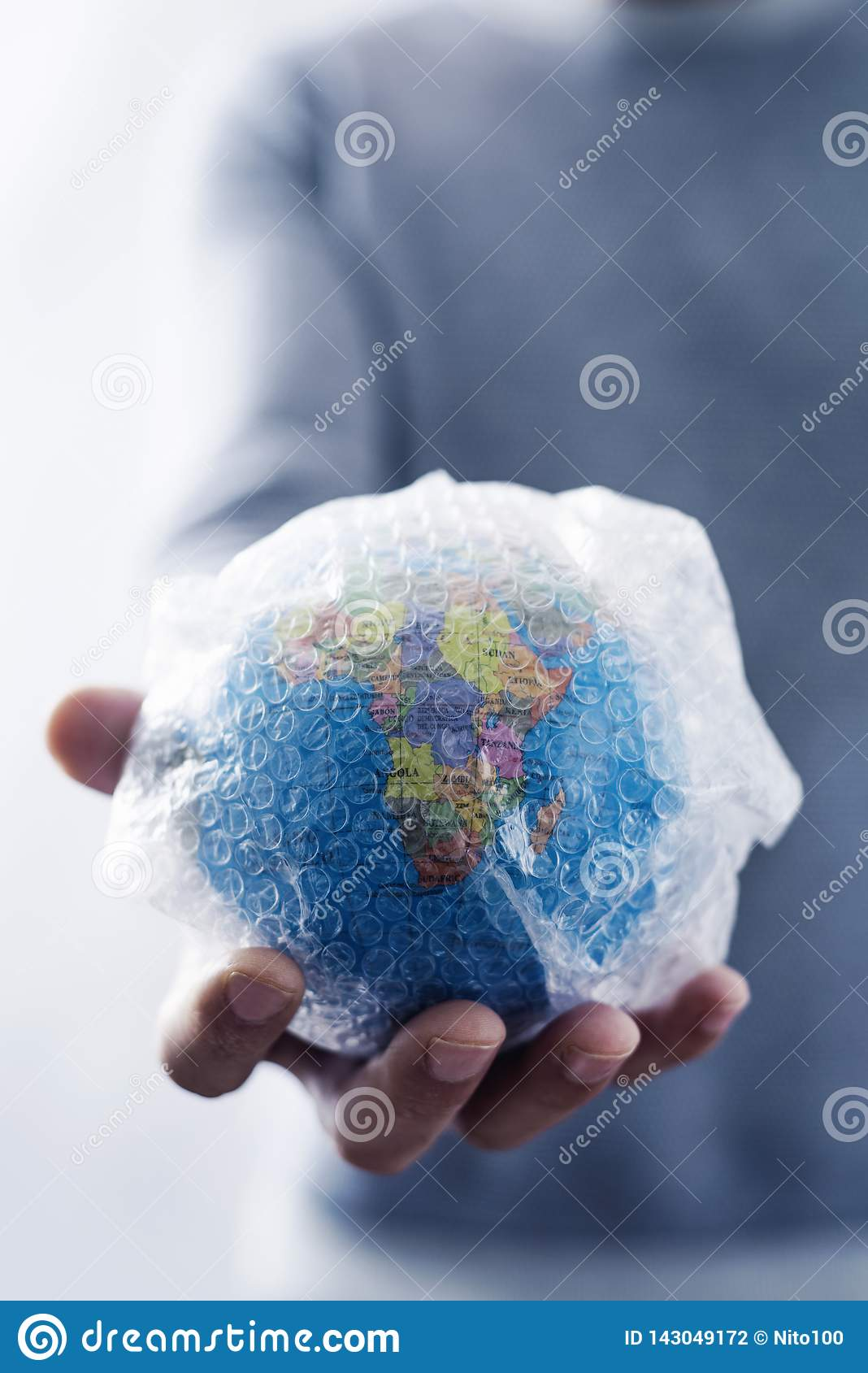 Man with a world globe wrapped in bubble wrap