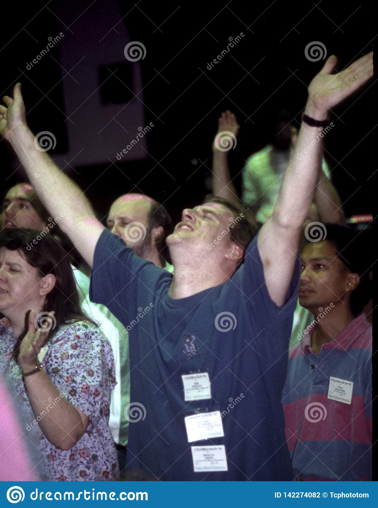 Man lifts hands in praise and worship during a church service in Lahnam, Maryland