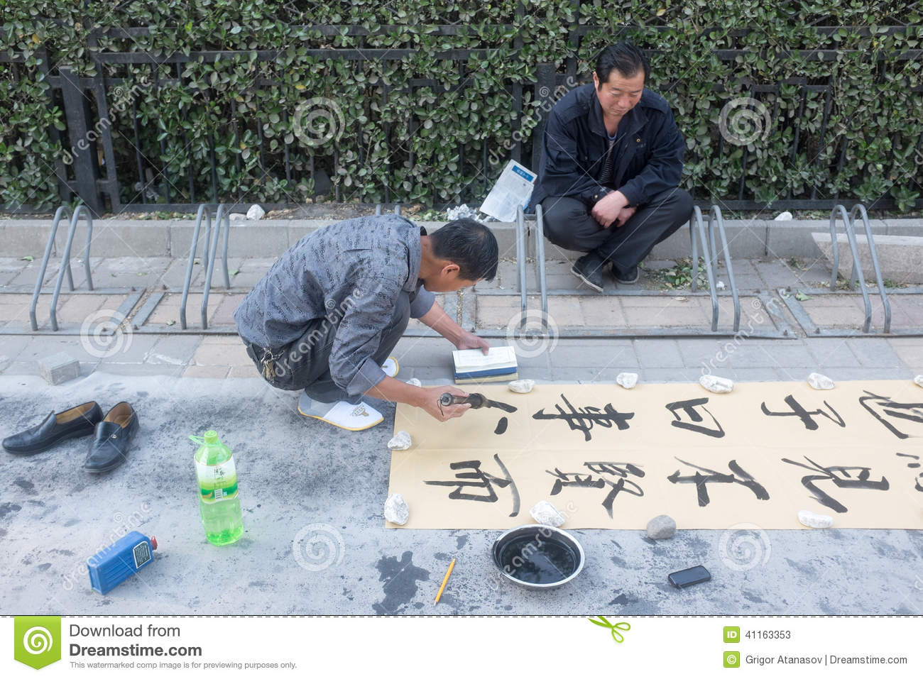 Man writing Chinese calligraphy