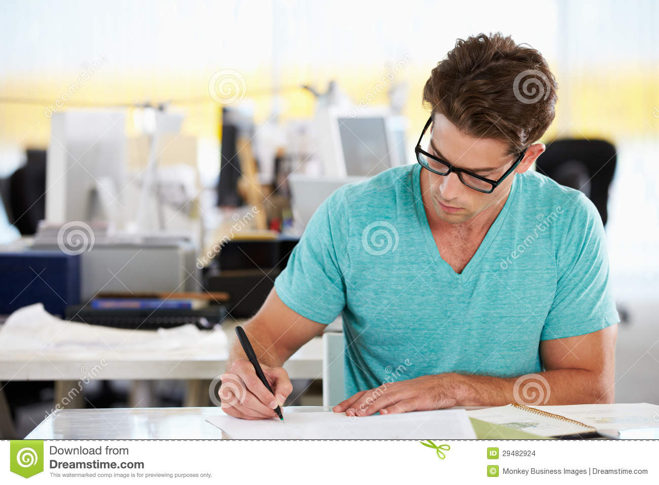 Man writing at desk in busy creative office stock photo