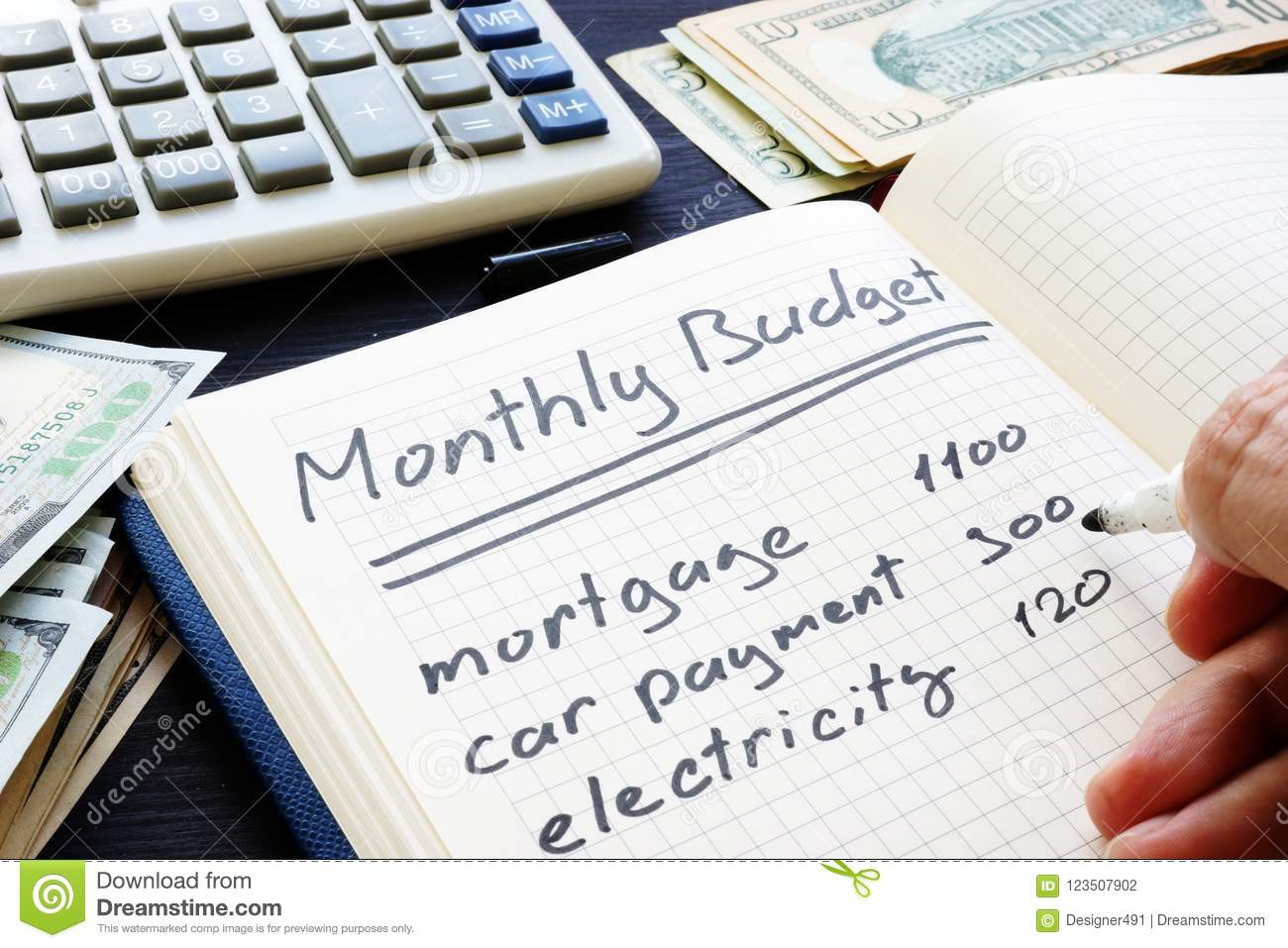 man is writing monthly budget plan home finances stock photo