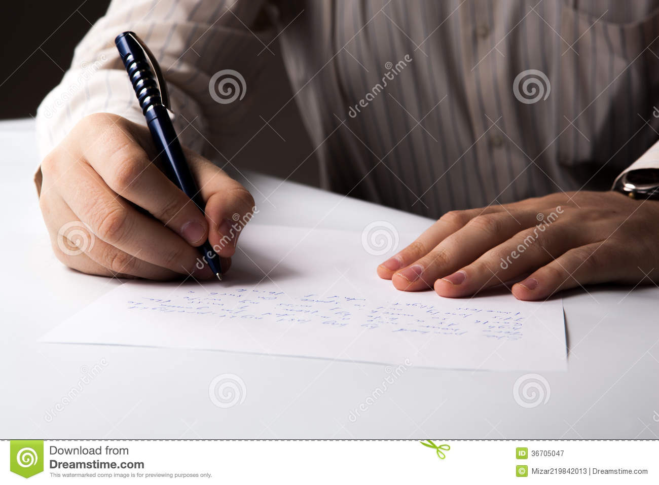 Man is writting on a sheet of paper