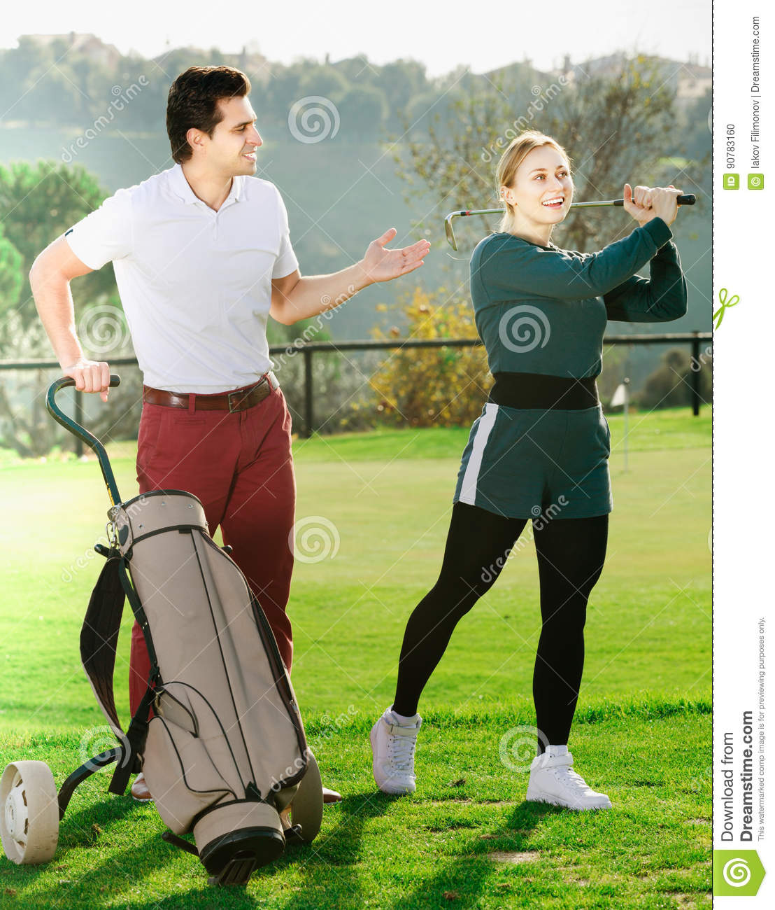 Man 30-35 years old is showing woman 25-29 years old to play golf