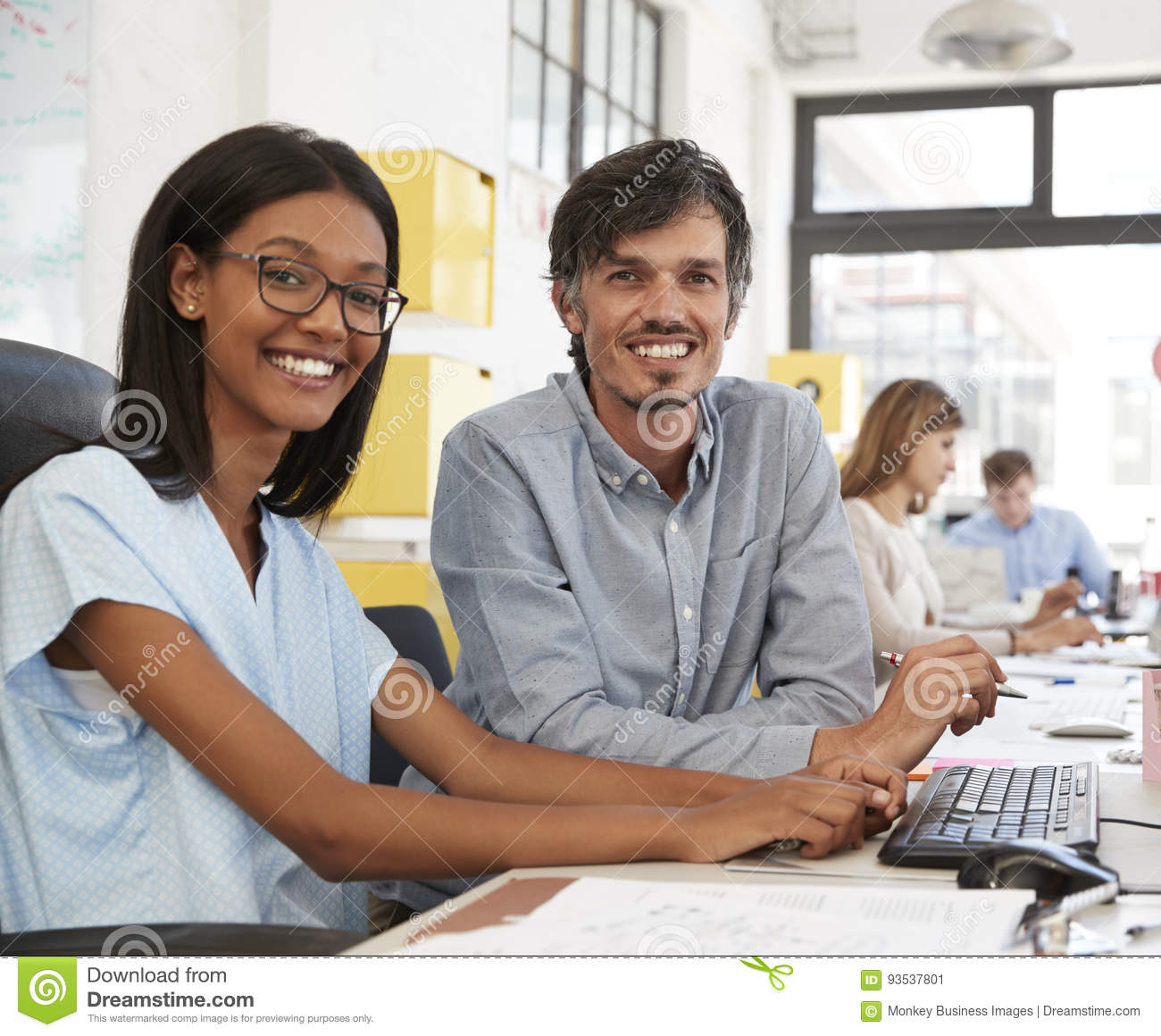 Man and young woman in open plan office looking to camera�