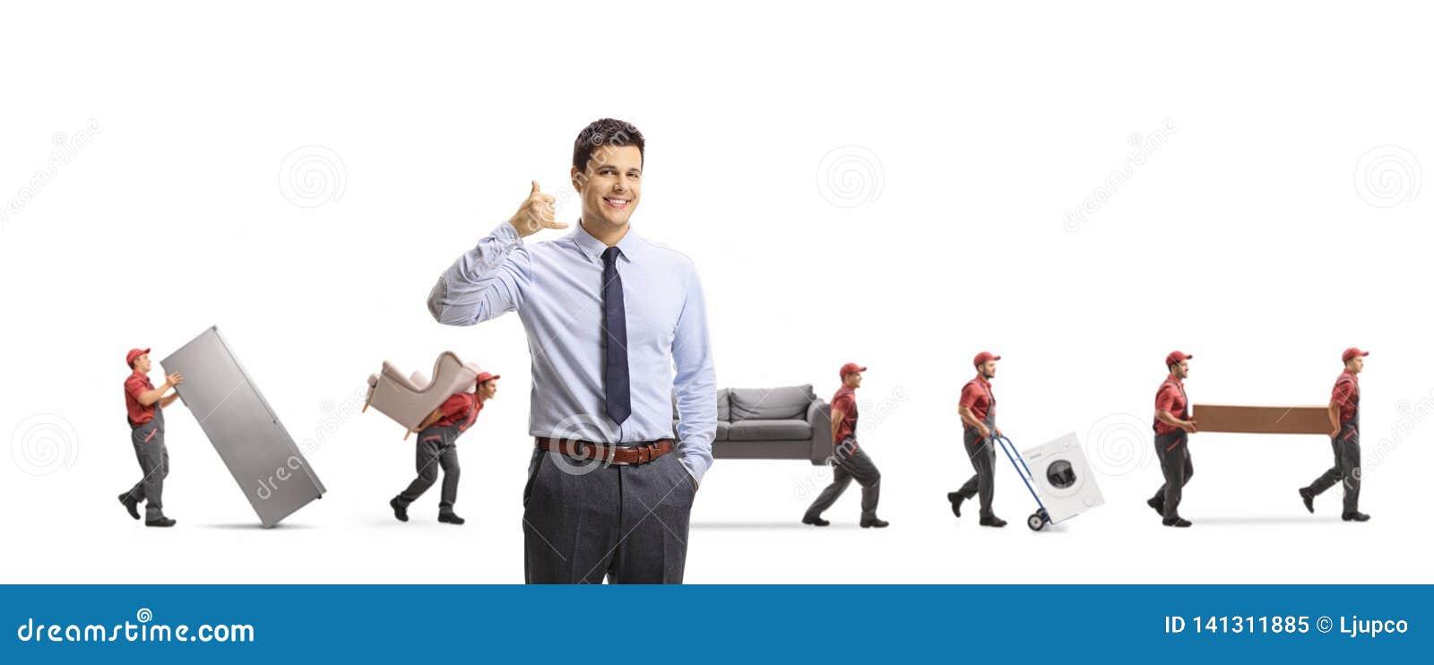 Manager einer Abbaufirma, die gestikuliert, uns anzurufen Zeichen und Arbeitskräfte tragen Möbel und appliences