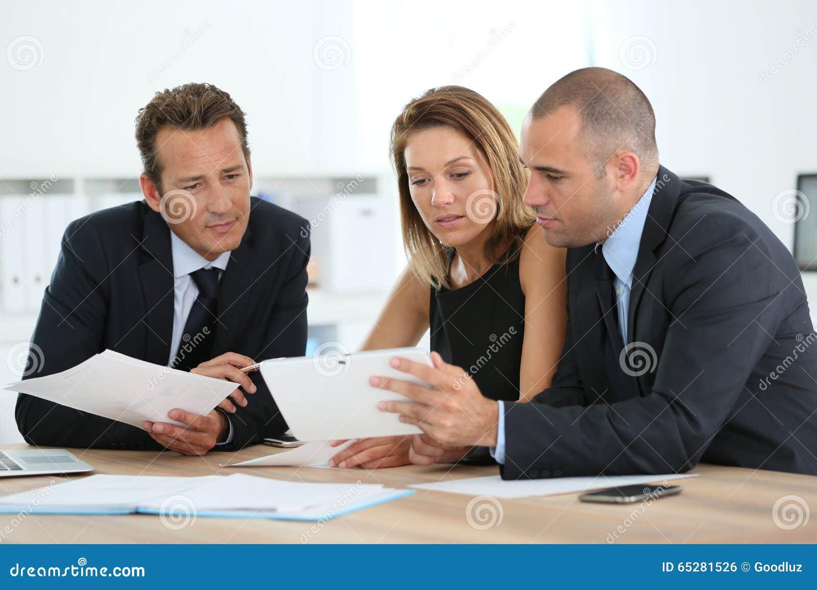 Manager met verkoopmensen die tablet gebruiken