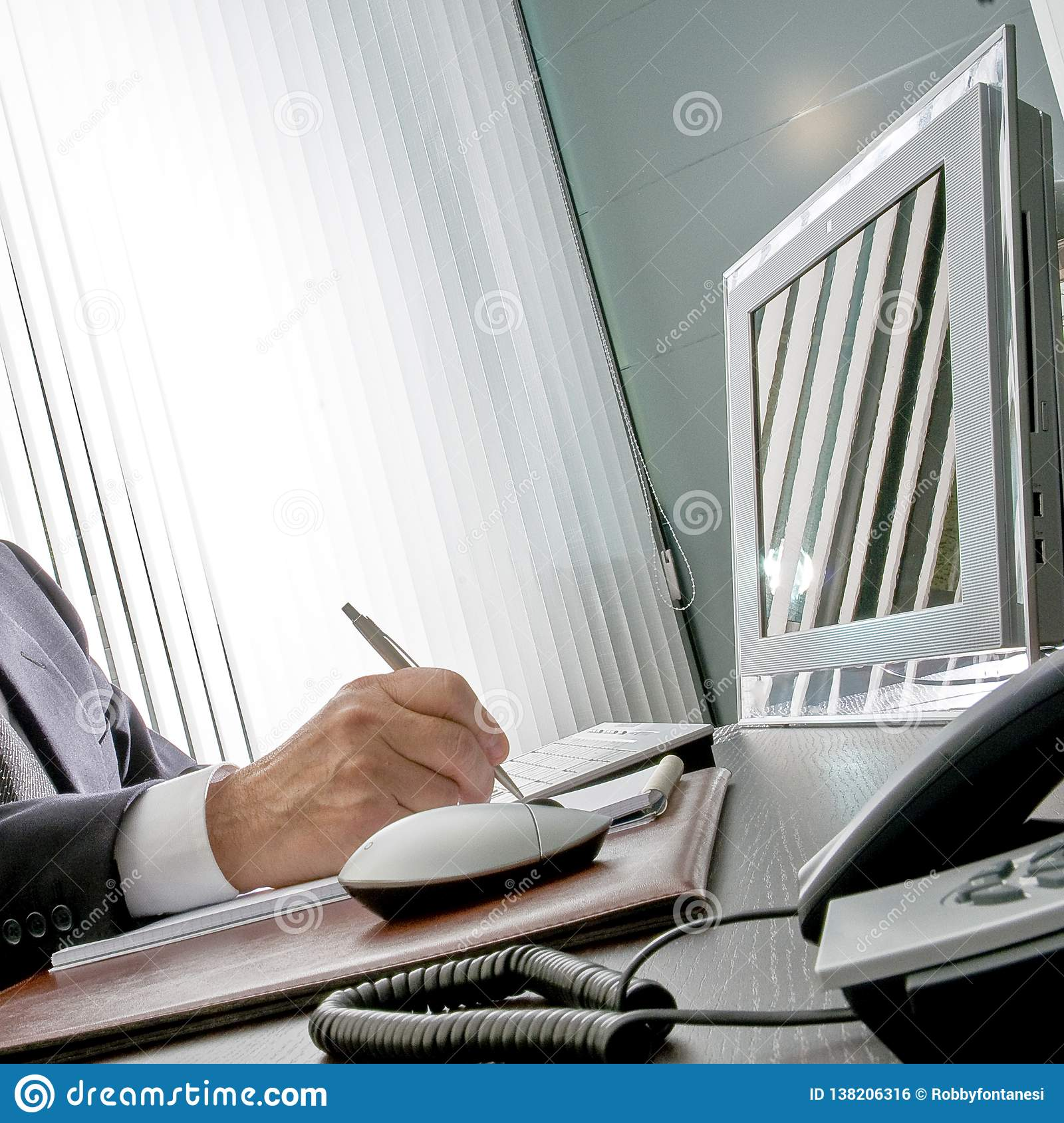 Manager at work. The expert hand of a businessman sitting at his desk, he holds the pen in front of his computer monitor that