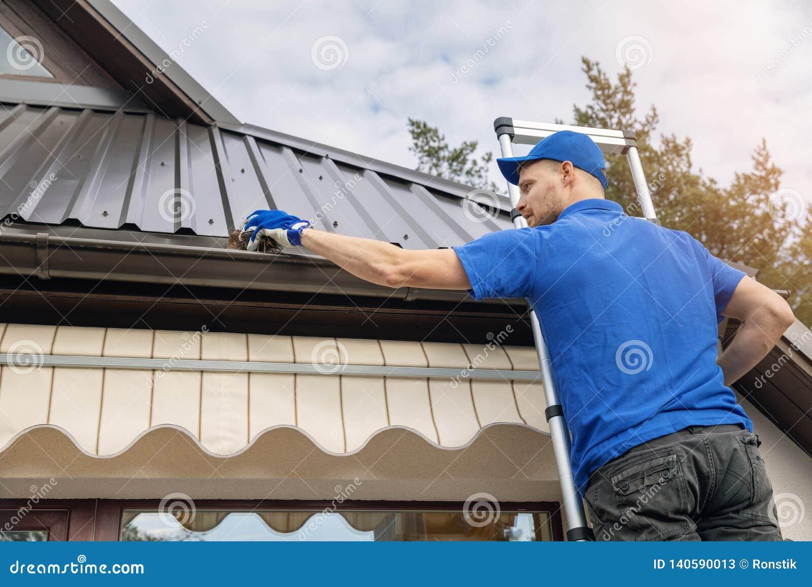 Mananseende på stege och den rengörande takstuprännan