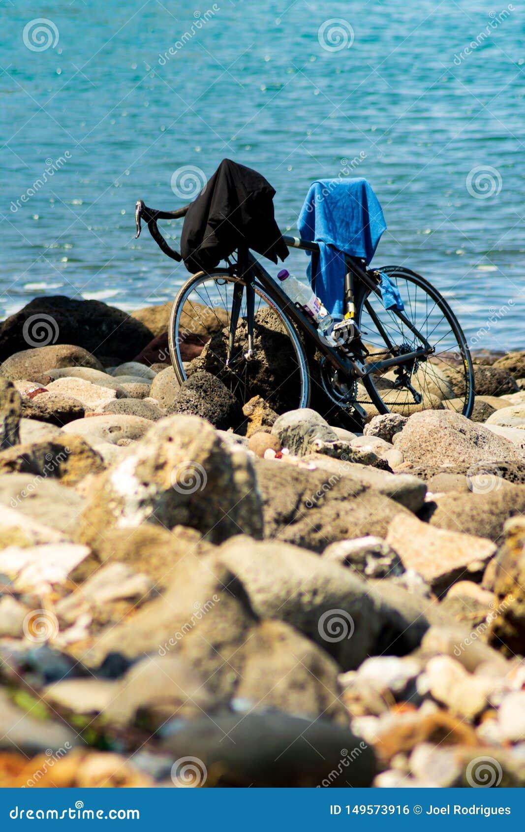 Manapany, Франция - 27-ое сентября 2018: Велосипед припаркованный на каменистом пляже пока владелец принимает заплыв