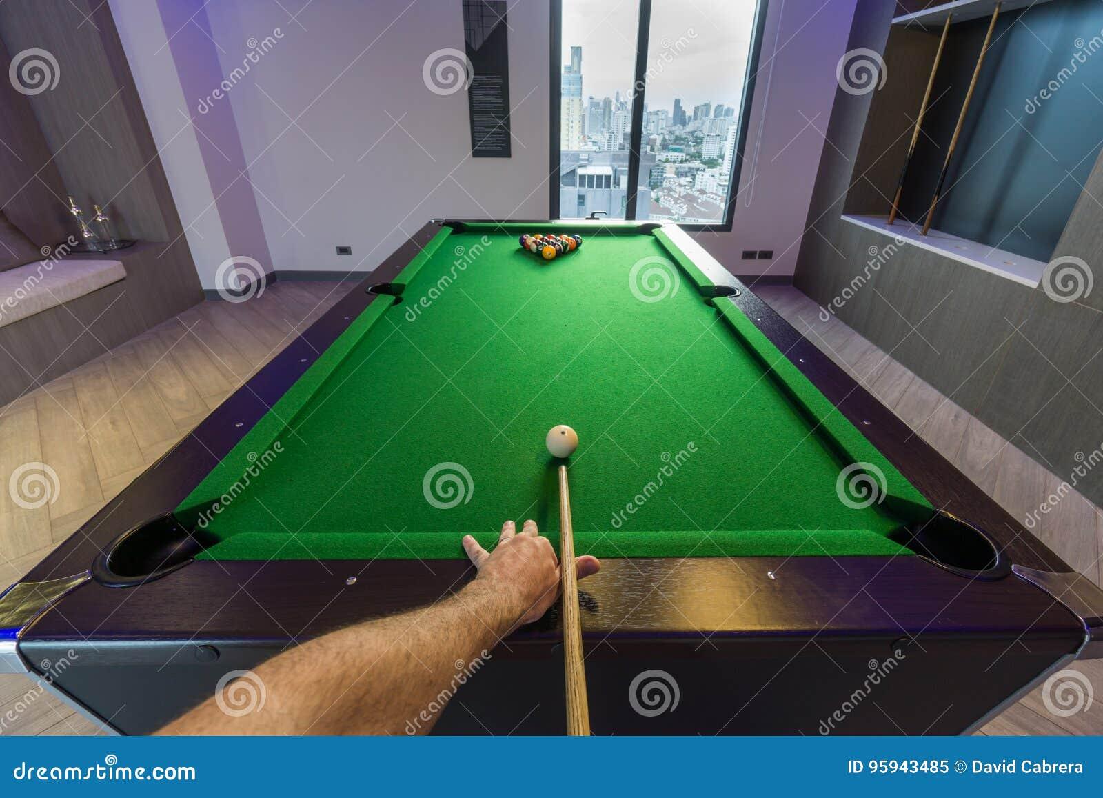Manarm som spelar den gröna tabellen för snookerpöl i ett modernt lekrum