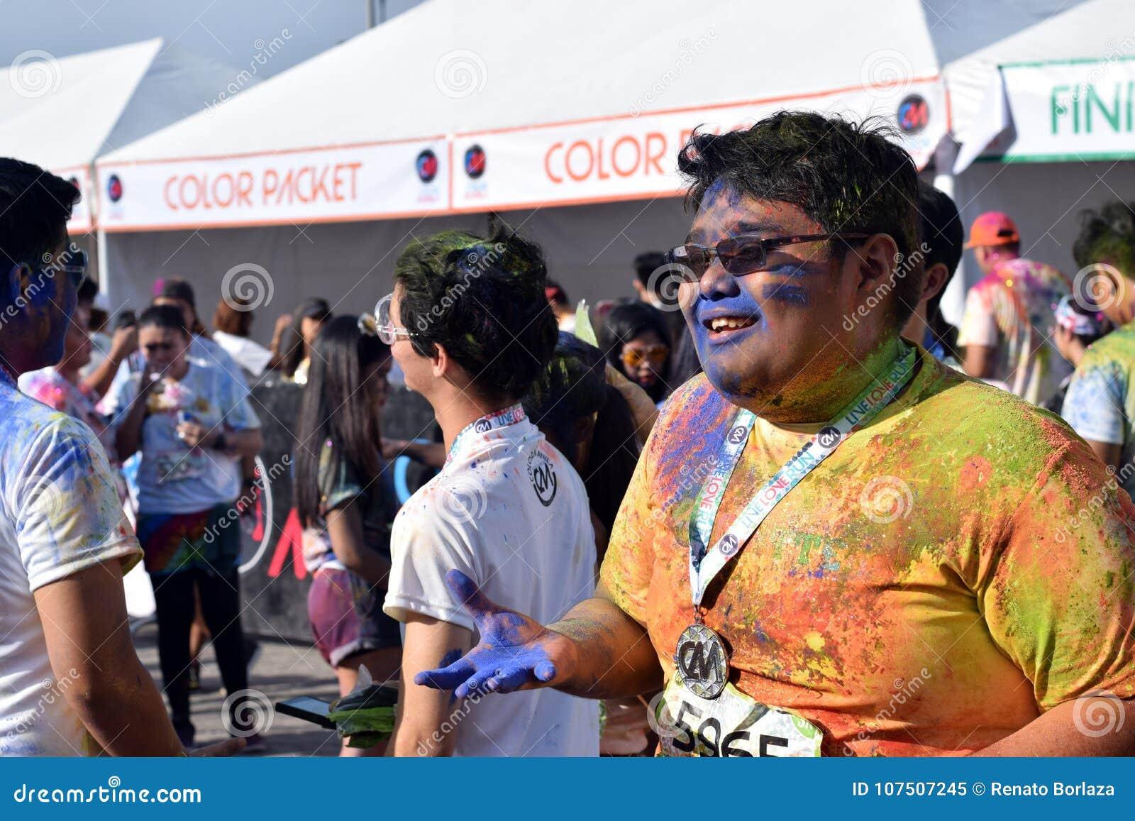 Manchado com as tinturas coloridas, jovens que têm o divertimento na corrida do brilho de Manila da cor