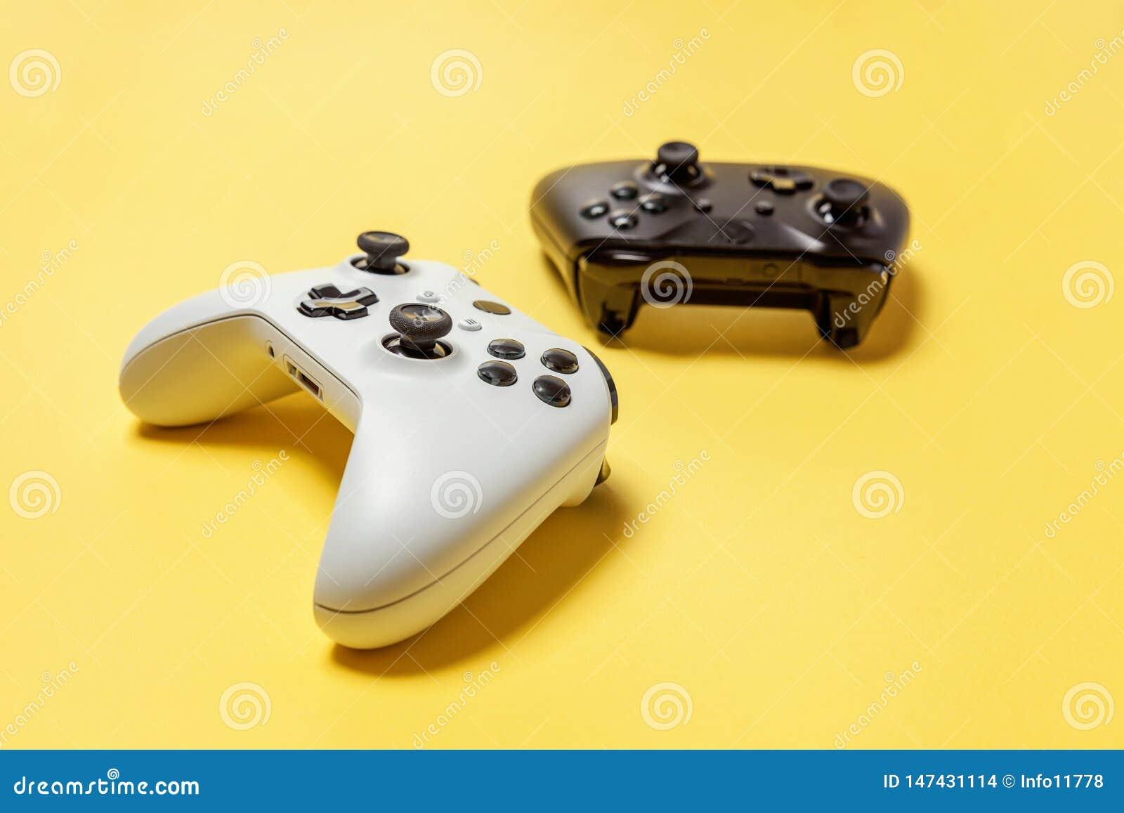 Manche dois branco e preto no fundo amarelo Conceito da confronta??o do controle do videogame da competi??o do jogo do computador