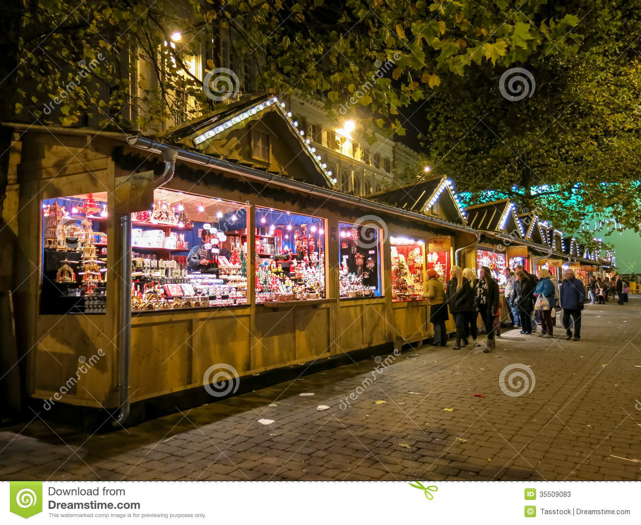 People and row of stalls on manchester christmas markets fair by night