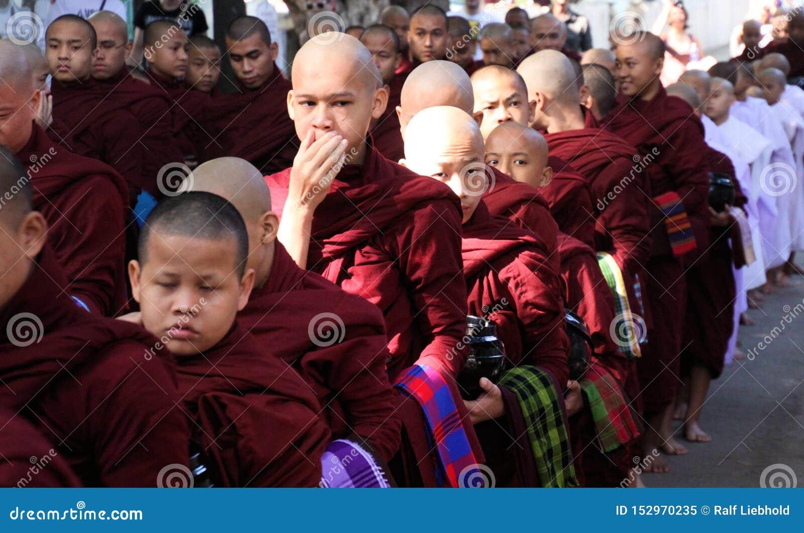 MANDALAY, MYANMAR - DECEMBER 18 2015: Optocht van Boeddhistische monniken bij Mahagandayon-Klooster in de vroege ochtend
