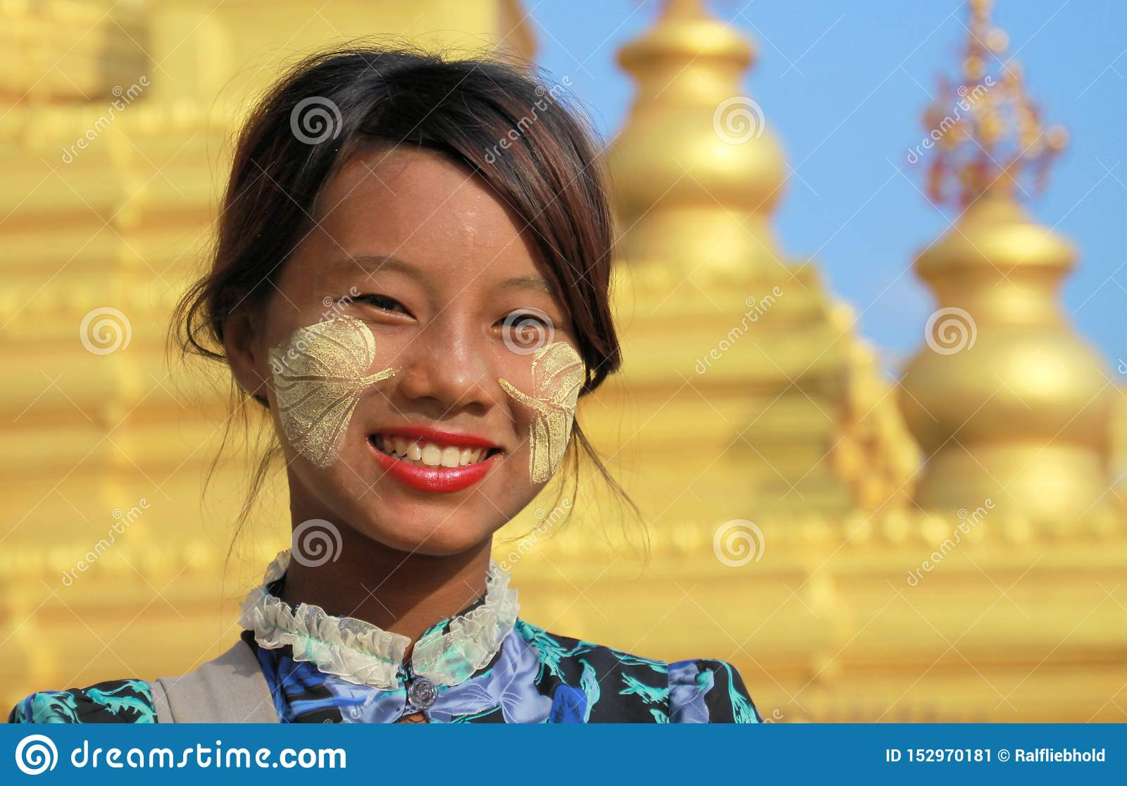 MANDALAY, MYANMAR - DECEMBER 17. 2015: Portrait of a Burmese girl with traditional Thanaka face painting in front of golden Pagoda
