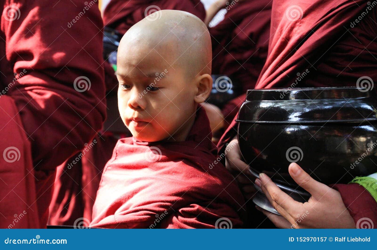 MANDALAY MYANMAR, GRUDZIEŃ, - 18 2015: Korowód mnisi buddyjscy przy Mahagandayon monasterem w wczesnym poranku