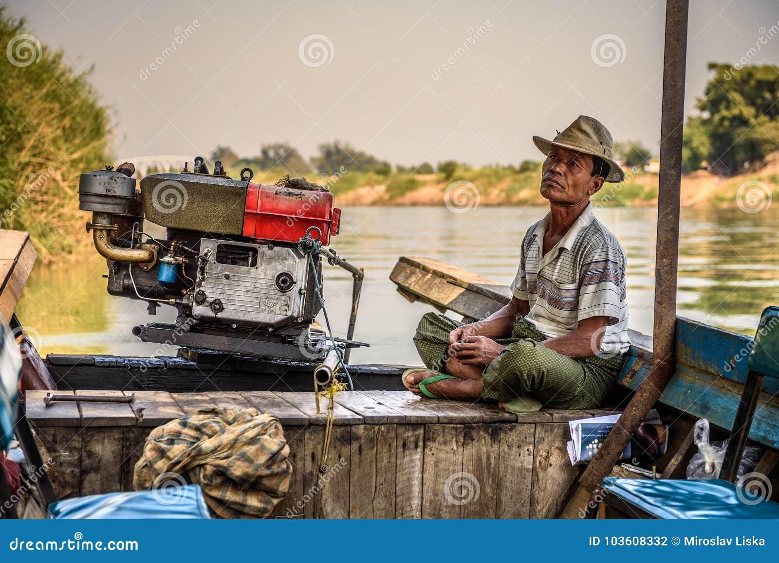 Burmese man controls a boat for travel the Mu River