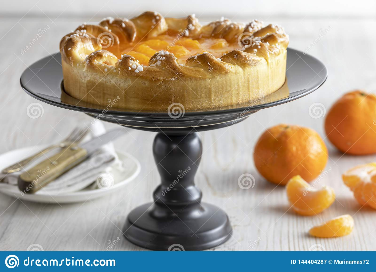 Mandarin cake and tangerines on rustic background