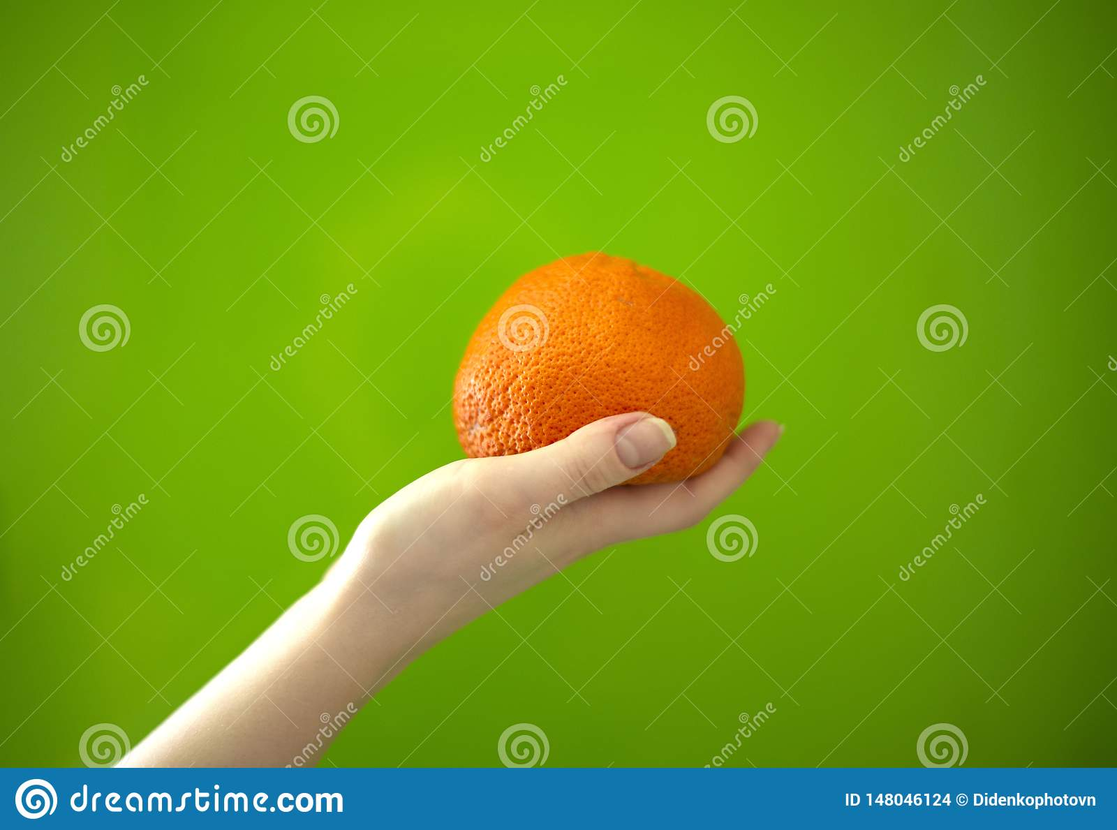 Mandarin in hand on a green background