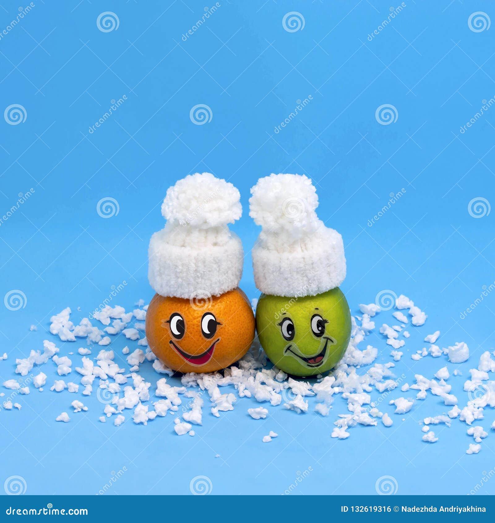 Mandarin och limefrukt i formen av roligt folk i vinter