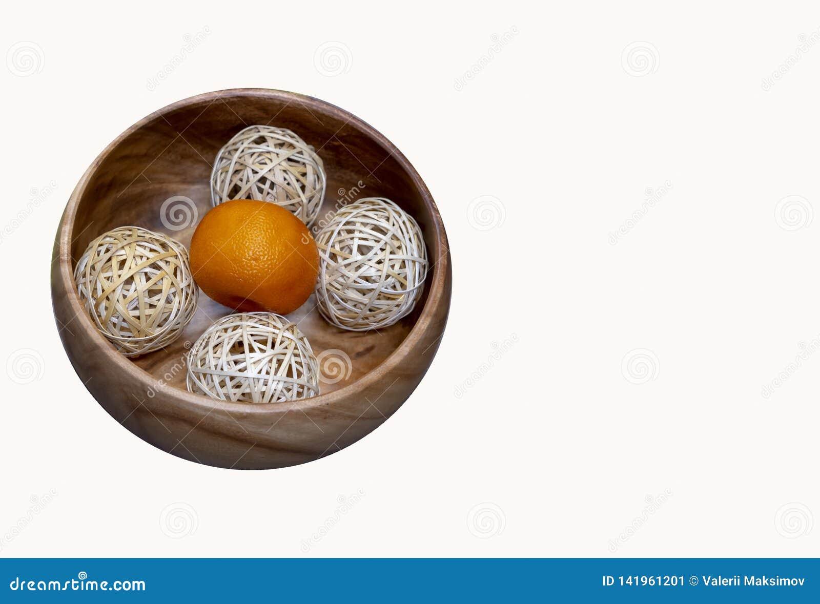 Mandarine mit Bällen in einer hölzernen Platte auf einem weißen Hintergrund