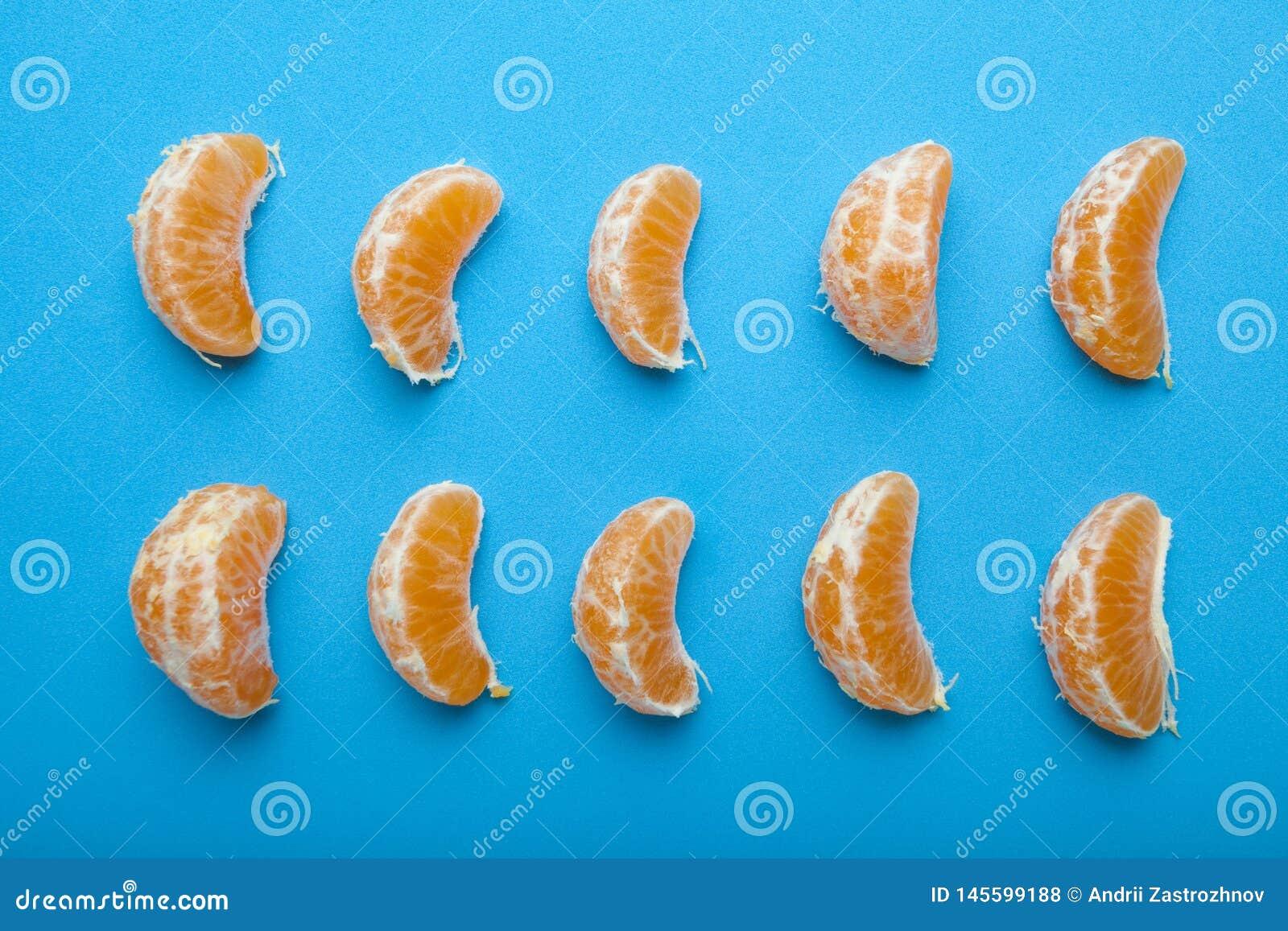 Mandarine plak op blauwe achtergrond Reeks van rijpe mandarine plak